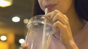 Adolescente que disfruta de la bebida dulce del vidrio plástico grande, bebidas para llevar almacen de metraje de vídeo