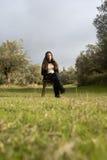 Adolescente que se sienta en una silla en el campo Fotografía de archivo libre de regalías