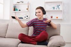 Adolescente que disfruta de música en auriculares en casa Fotografía de archivo libre de regalías
