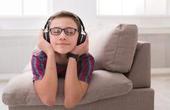 Adolescente que disfruta de música en auriculares en casa Imagen de archivo