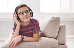 Adolescente que disfruta de música en auriculares en casa Imagen de archivo libre de regalías