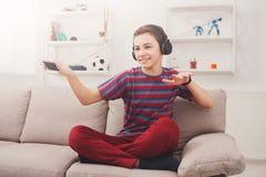 Adolescente que disfruta de música en auriculares en casa Fotos de archivo