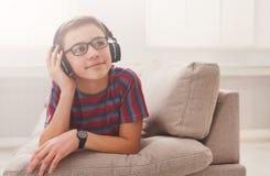Adolescente que disfruta de música en auriculares en casa Foto de archivo libre de regalías
