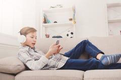 Adolescente que disfruta de música en auriculares en casa Foto de archivo