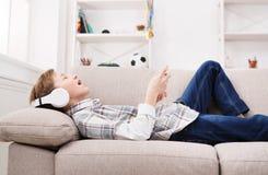 Adolescente que disfruta de música en auriculares en casa Imágenes de archivo libres de regalías