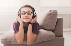 Adolescente que disfruta de música en auriculares en casa Imagenes de archivo