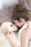 Adolescente que duerme con su perro Foto de archivo