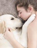 Adolescente que duerme con su perro Imagen de archivo libre de regalías