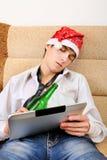 Adolescente que duerme con una cerveza y una tableta Foto de archivo