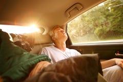 Adolescente que duerme en el asiento trasero de un coche en un viaje Imagen de archivo libre de regalías