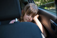 Adolescente que duerme en el asiento trasero del coche Fotos de archivo libres de regalías