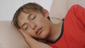 Adolescente que duerme en el sofá Primer del muchacho adolescente caucásico en camiseta roja que duerme en el sofá de cuero beige almacen de metraje de vídeo