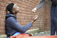 Adolescente que duerme en la calle que es dada el dinero Imágenes de archivo libres de regalías