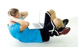 Adolescente que ejercita mientras que usa su computadora portátil Imagen de archivo