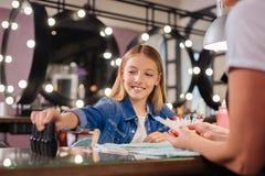 Adolescente que elige la botella del esmalte de uñas para la manicura Fotos de archivo