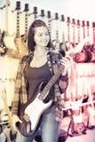 Adolescente que elige la guitarra eléctrica Fotografía de archivo libre de regalías