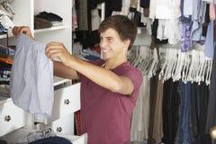 Adolescente que elige la ropa de guardarropa en dormitorio Fotos de archivo