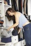 Adolescente que elige la ropa de guardarropa en dormitorio Imagen de archivo