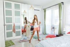 Adolescente que elige la ropa en armario Foto de archivo
