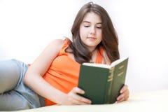 Adolescente que encontra-se e que lê um livro Fotos de Stock Royalty Free