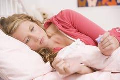 Adolescente que encontra-se em sua cama fotografia de stock