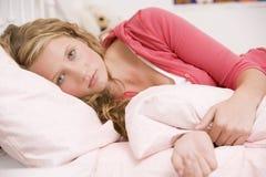 Adolescente que encontra-se em sua cama que olha doente Fotografia de Stock