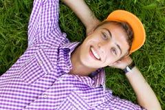 Adolescente que encontra-se para baixo na grama Fotos de Stock Royalty Free