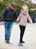 Adolescente que enseña al skateboarding de la pequeña hermana Imagenes de archivo