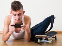 Adolescente que entierra en teléfono móvil Imagen de archivo libre de regalías