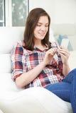 Adolescente que envía el mensaje de texto del teléfono móvil en casa Imagen de archivo libre de regalías