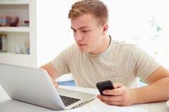 Adolescente que envía el mensaje de texto mientras que estudia en el ordenador portátil Imagen de archivo libre de regalías