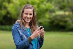 Adolescente que envía un texto con su teléfono móvil Fotos de archivo libres de regalías