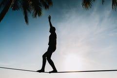 Adolescente que equilibra en slackline con la opinión del cielo Imagen de archivo