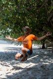 Adolescente que equilibra en slackline con la opinión del cielo sobre la playa Imagen de archivo