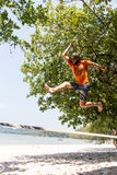 Adolescente que equilibra en slackline con la opinión del cielo sobre la playa Fotos de archivo