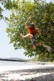 Adolescente que equilibra en slackline con la opinión del cielo sobre la playa Imagenes de archivo