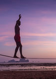 Adolescente que equilibra en slackline con la opinión del cielo sobre la playa Imágenes de archivo libres de regalías