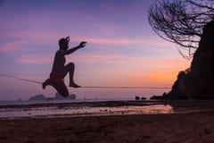 Adolescente que equilibra en slackline con la opinión del cielo sobre la playa Foto de archivo libre de regalías