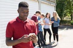 Adolescente que es tiranizado por el mensaje de texto imagen de archivo