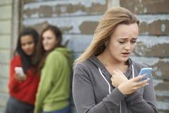 Adolescente que es tiranizado por el mensaje de texto Foto de archivo libre de regalías