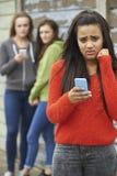 Adolescente que es tiranizado por el mensaje de texto Imagenes de archivo