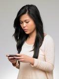Adolescente que es tiranizado por el mensaje de texto en el teléfono móvil Fotografía de archivo libre de regalías