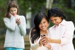 Adolescente que es tiranizado por el mensaje de texto en el teléfono móvil Imágenes de archivo libres de regalías