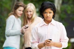 Adolescente que es tiranizado por el mensaje de texto en el teléfono móvil Foto de archivo libre de regalías
