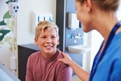 Adolescente que es tranquilizado por el doctor In Hospital Room Fotos de archivo