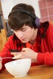 Adolescente que escucha el jugador MP3 mientras que come Foto de archivo
