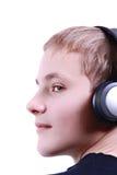 Adolescente que escucha la música con el auricular Fotos de archivo