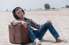 Adolescente que escucha la música en la playa Foto de archivo libre de regalías