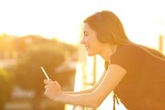 Adolescente que escucha la música en la puesta del sol en un balcón Imagen de archivo libre de regalías