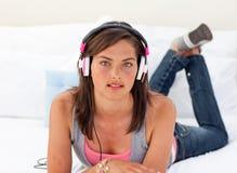 Adolescente que escucha la música en su cama Fotos de archivo